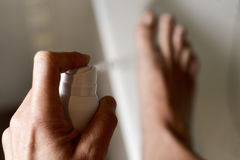 应用防臭剂的年轻人于他的脚 免版税库存照片