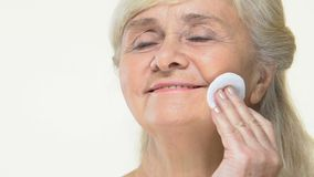 应用面孔化妆水的愉快的资深妇女由化装棉,组成去膜剂皮肤护理 影视素材