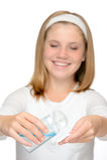 应用面孔清洁化妆水的年轻微笑的女孩 免版税图库摄影