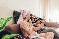应用面膜和黄瓜在眼睛的母亲和她的成人女儿 获得的妇女在家使和乐趣变冷 库存照片