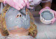 应用面膜的美容师于问题皮肤 有的年轻女人面孔氧化物介质 图库摄影