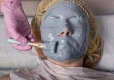 应用面膜的美容师于问题皮肤 有的年轻女人面孔氧化物介质 库存图片