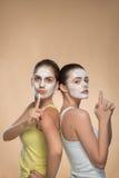 应用面部奶油色面具的两个美丽的女孩和 库存图片