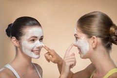 应用面部奶油色面具的两个美丽的女孩和 库存照片