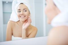 应用面部润湿的奶油的美丽的少妇 Skincare概念 免版税库存照片