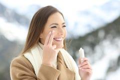 应用面部润肤霜奶油的愉快的夫人在冬天 免版税库存照片