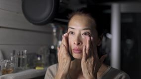 应用面霜的亚裔中间年迈的妇女在厨房里 影视素材