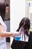 应用颜色女性顾客的美发师在沙龙,做染发剂 免版税图库摄影