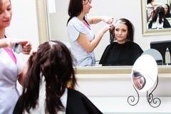 应用颜色女性顾客的美发师在沙龙,做染发剂 免版税库存图片