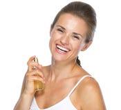 应用香水的微笑的少妇画象  免版税库存图片
