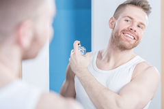 应用香水的英俊的人 免版税图库摄影