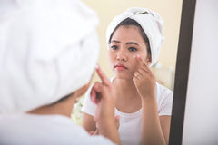 应用skincare化妆水的妇女入她的面孔 库存图片