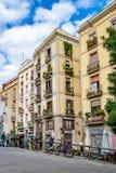 底层商店、公寓与垂悬在阳台的植物,停放的走,在巴塞罗那的自行车和人们 免版税库存图片