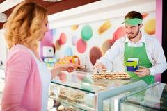 年轻店主在卖甜点的工作对顾客 免版税库存照片