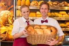 店主在提出在篮子的面包师的商店小圆面包 免版税库存图片