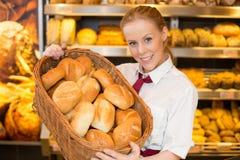 店主在提出在篮子的面包师的商店小圆面包 库存照片