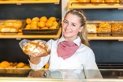 店主在提出面包的面包店对客户 免版税库存照片