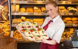 店主在显示三明治的面包店对顾客 免版税库存图片