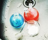 废品在实验室,与上色的医学玻璃红色和蓝色液体 免版税图库摄影