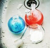 废品在实验室,与上色的医学玻璃红色和蓝色液体 免版税库存图片