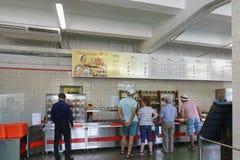 度假者在一个风格化苏联餐厅选择盘 题字在俄国餐厅?1和菜单在星期 库存图片