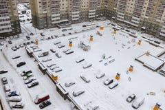 庭院公寓在冬天 在围场停车处、操场和汽车 图库摄影