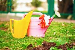 庭院喷壶和手套在草坪 免版税图库摄影