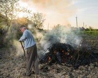 庭院工作 农夫燃烧干分支 库存照片