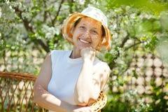 庭院愉快的成熟春天妇女 免版税库存图片