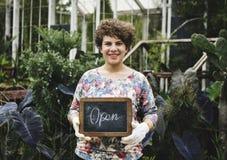 庭院拿着一个开放标志的店主 图库摄影