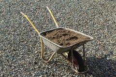 庭院推车在岩石站立,装载用沙子 库存图片