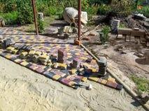 庭院环境美化与五颜六色的美丽的铺路板的,未完成的工作 免版税库存照片