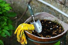 庭院瓢和庭院手套在花盆 免版税库存照片