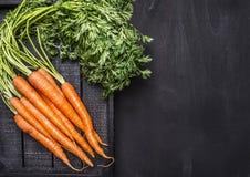 从庭院的新鲜的红萝卜在woborder,文本木土气背景顶视图的地方的一个黑木箱的 免版税库存照片