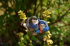 庭院的陶瓷装饰品鸟在植物中在阳光下 免版税库存照片