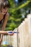 绘庭院篱芭的妇女 免版税库存照片