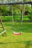 庭院红色塑料儿童的摇摆在庭院里 免版税库存图片