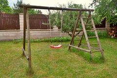 庭院红色塑料儿童的摇摆 图库摄影