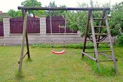 庭院红色塑料儿童的摇摆 库存照片
