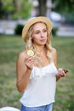 庭院背景的Preety少妇 帽子的一个白肤金发的女孩 一个女孩用柠檬 异乎寻常的饮食 健康生活方式 库存照片