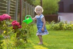 给水庭院花的逗人喜爱的小女孩 免版税图库摄影