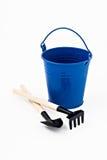 庭院被隔绝的铁锹、犁耙和蓝色金属桶 免版税库存照片