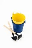 庭院被隔绝的铁锹、犁耙和蓝色金属桶 免版税库存图片