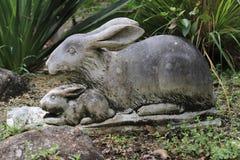 庭院雕塑野兔妈妈和小的野兔 库存图片