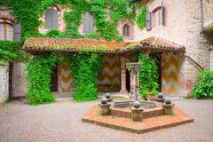 庭院,与一个老喷泉的典型的中世纪法院 免版税库存照片