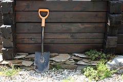 庭院-在一个用木材建造的水井的铁锹 免版税库存图片