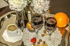 康乃馨花束在一个水晶花瓶,无奶咖啡,与一个瓶的老水晶玻璃的利口酒 免版税库存图片