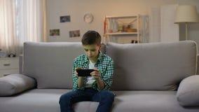 延迟和打在智能手机的学龄前男孩比赛,小配件瘾 股票录像