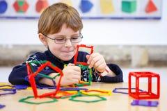 建立与塑料块的小孩男孩几何图 免版税库存照片