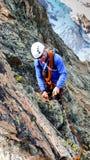 建立与岩钉的男性山指南传统套住姿态从一个高高山峰顶坐式下降法 库存照片